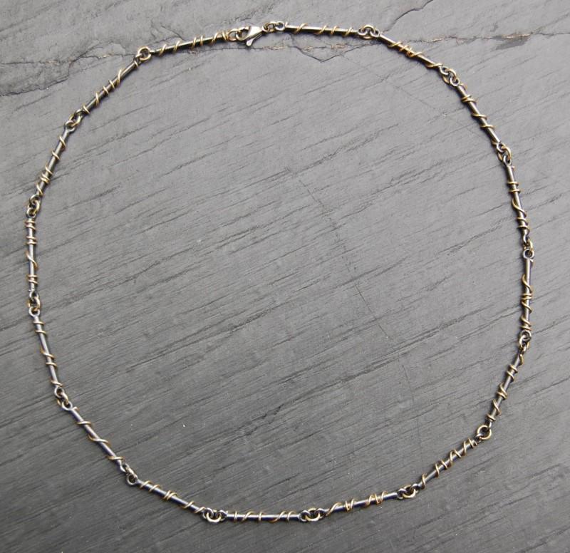 Die Kette ist aus mit Gold umwickelten Silberstäbchen gebaut und hat goldene Verbindungsösen.