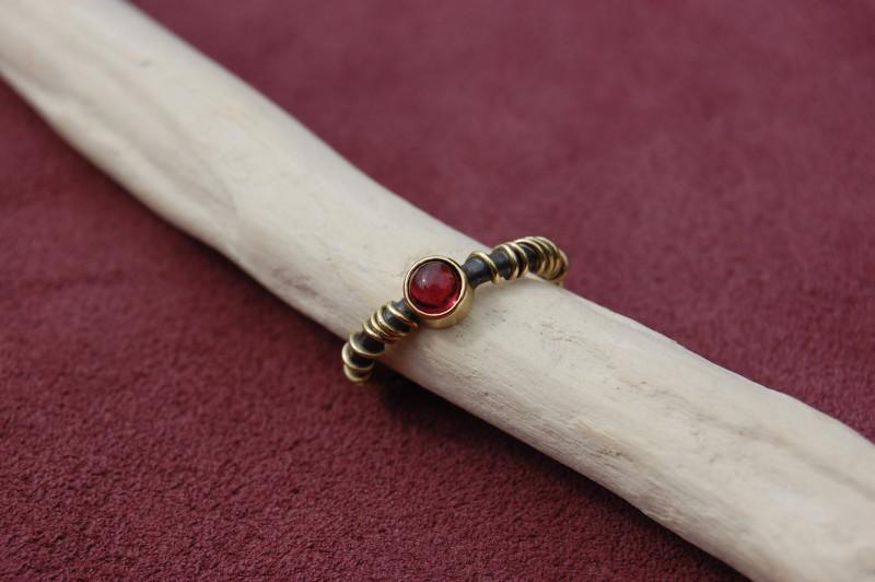 Der Ring ist in geschwärztem Silber mit einer Wicklung in 750er Gelbgold gefertigt. Blickfang ist der rote Turmalin in der Goldfassung.