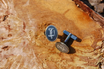 Diese Manschettenknöpfe aus geschwärztem Silber wurden mit einem Goldrand versehen und nach Kundenwunsch graviert.